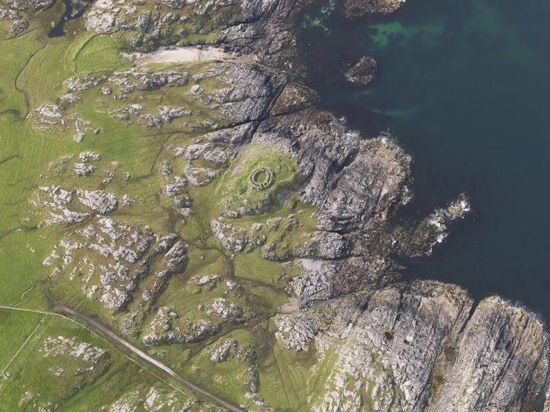 Oblique aerial view of the remains of Dun Mor Vaul broch on the Island of Tiree, taken from the SE.