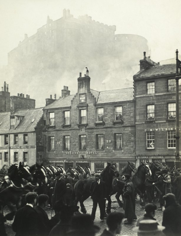 View of horses outside Beehive Hotel, and also showing parts of The Black Bull and 26 Grassmarket, Edinburgh with the Castle in the background.  Titled: 'The one o'clock gun. Castle from Grassmarket. All Hallow Fair. November 1905' PHOTOGRAPH ALBUM No.30: OLD EDINBURGH ALBUM