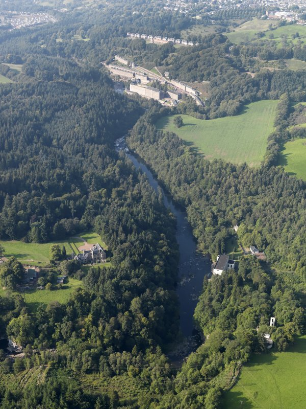 General oblique aerial view centred on Corehouse country house and Bonnington power station with New Lanark village beyond, taken from the S.