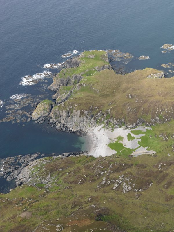 General oblique aerial view of Port nam Fliuchan looking towards Dun Uragaig, taken from the SSE.