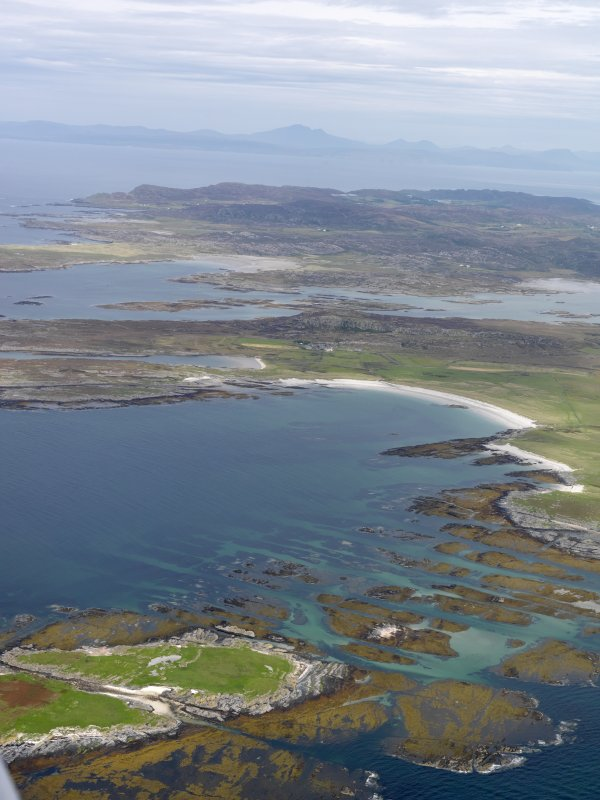Oblique aerial view of the W coast of Oronsay, looking towards Colonsay and Mull, taken from the SW.