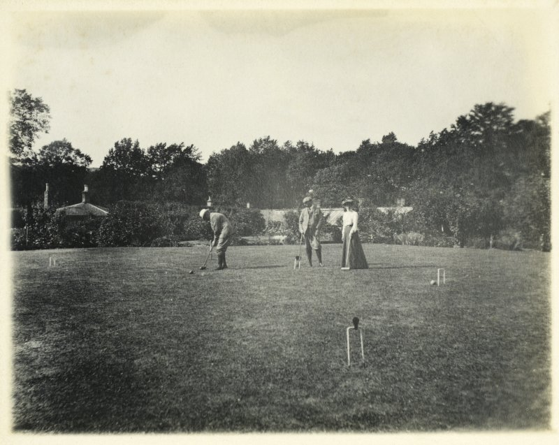 View of garden buildings and croquet lawn with group of people playing croquet, probably at Inchrye Abbey.