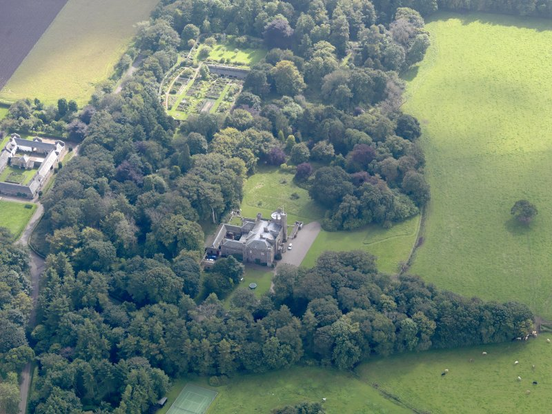 General oblique aerial view of the Dunninald estate, centred on Dunninald Castle, taken from the NNW.