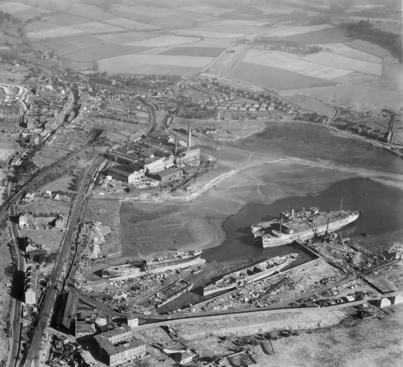 Oblique aerial view centred on Thomas Ward and Sons Shipbreaking Yard and Caldwells Paper Mill, Inverkeithing, in 1947, facing north-east. The vessels include a mine damaged large bulk carrier, a small bulk carrier, two large passenger liners and a general cargo ship.