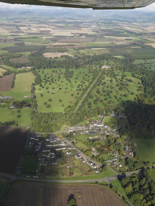 General oblique aerial view of Glamis Castle and its Policies with Glamis Village in the immediate foreground, taken from the SSE.