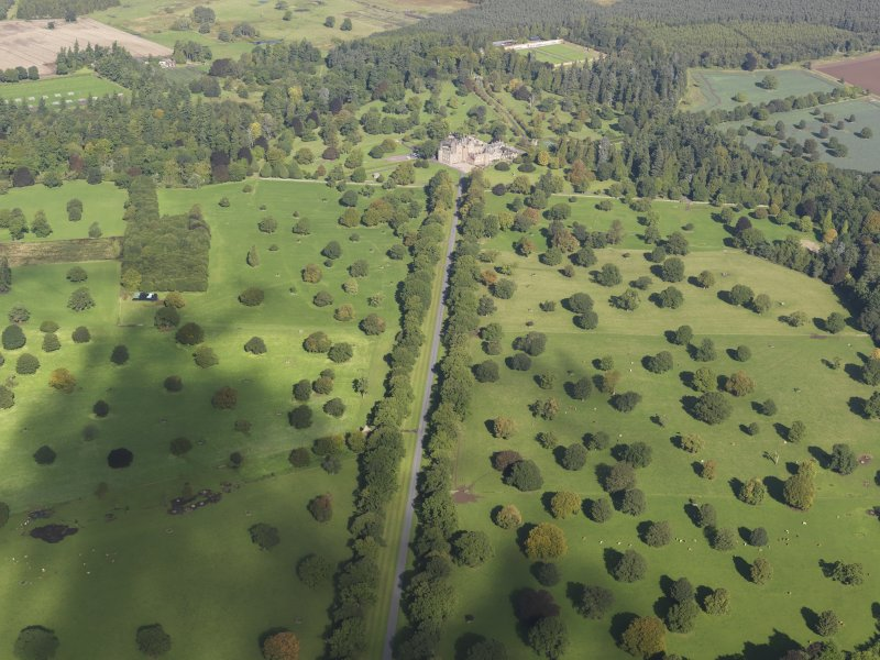 General oblique aerial view of the policies of Glamis Castle, looking up the Avenue centred on Glamis Castle, taken from the South.