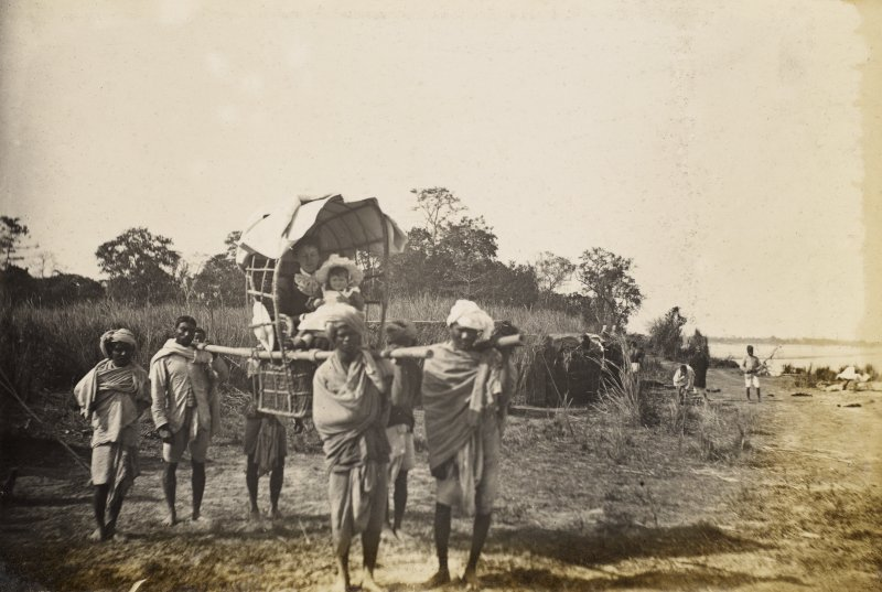 View of woman and child being carried, possibly in India