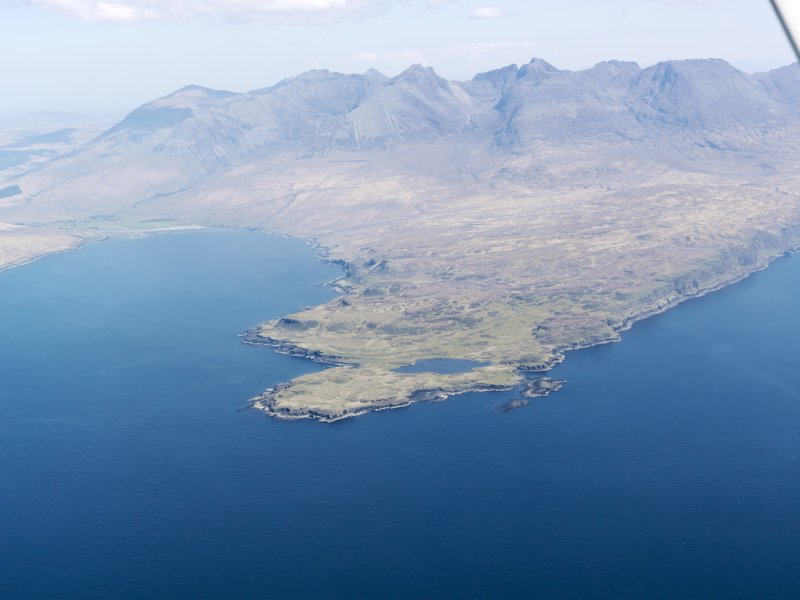 General oblique aerial view centred on Loch na h-Airde, the 'Viking Canal' and Rubh' an Dunain with the Cuillin Hills in the background, taken from the SW.