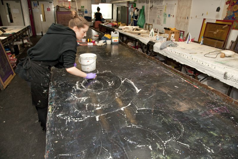 View of student cleaning the printing tables of the printmaking workshop within Newbery Tower