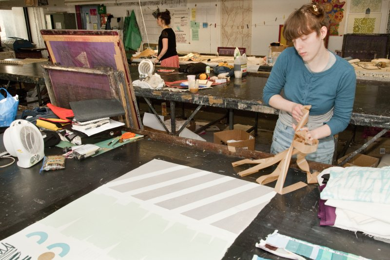View of student working at the printing tables of the printmaking workshop within Newbery Tower