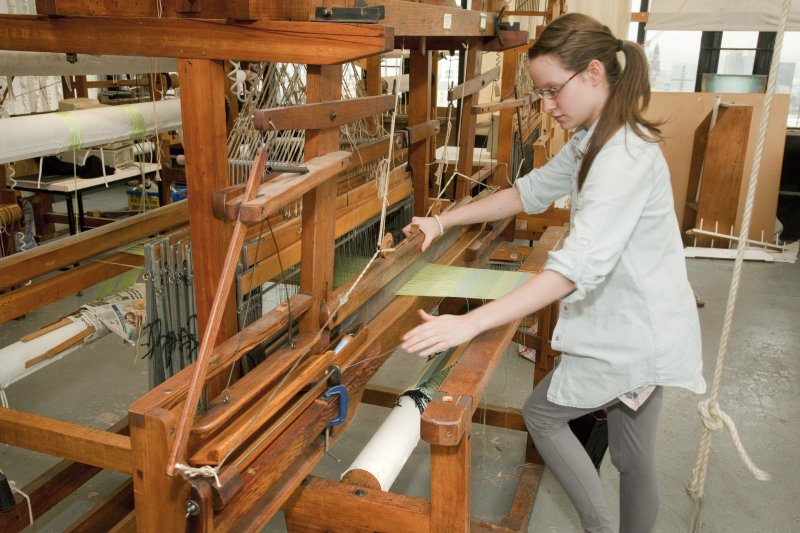 View of student working at a loom within the weaving studio of the Newbery Tower