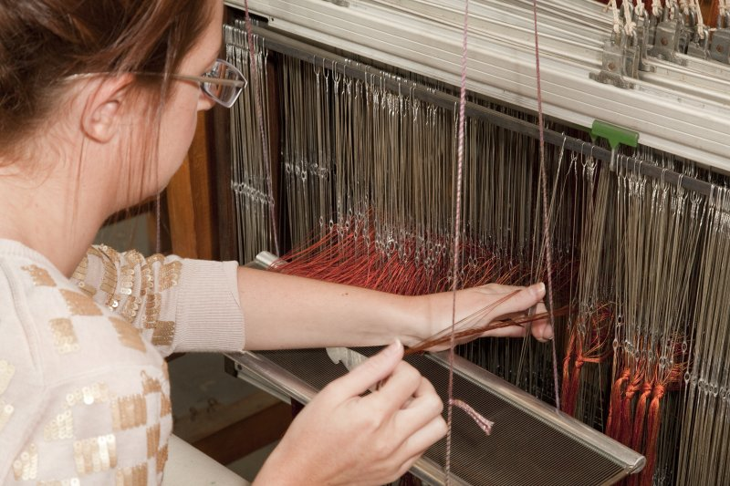 Detail of student working a loom within the weaving studio of the Newbery Tower
