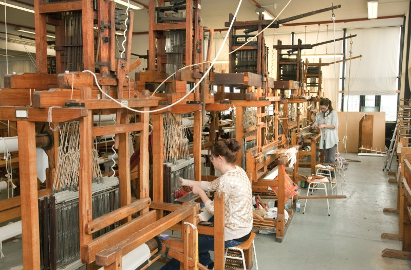 View of students working the looms within the weaving studio of the Newbery Tower