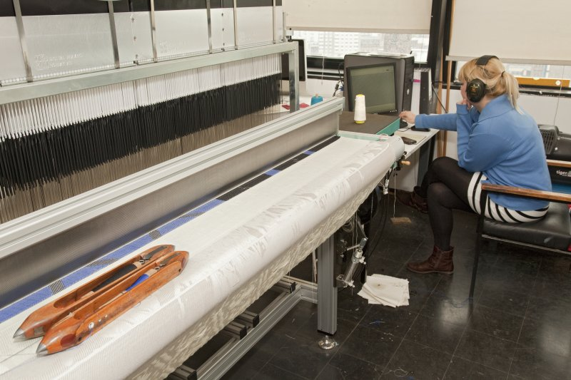 View of student working a computerised loom within the weaving studio of Newbery Tower