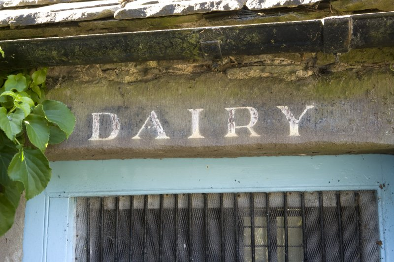 Courtyard, N range, detail of 'dairy' sign on lintel above door