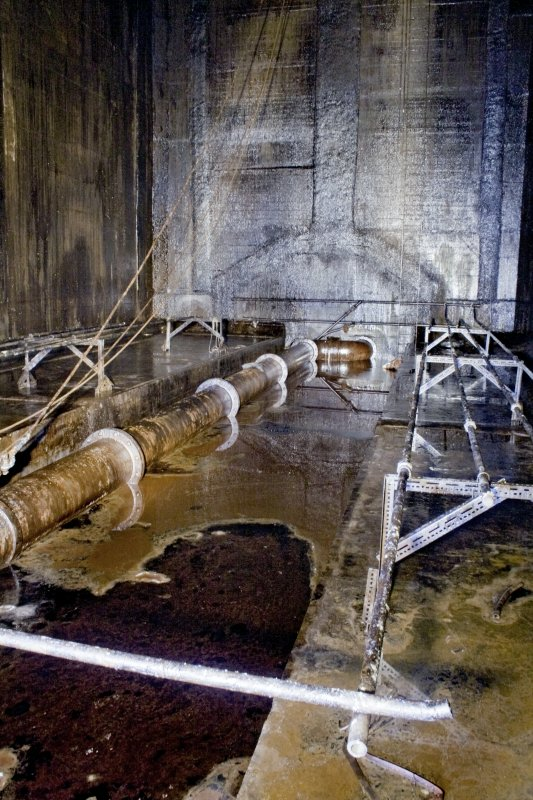 Interior. Details of SW end of tank 1, showing the 18-inch diameter swing arm pipe through which the oil entered and exited the tank. Also visible are the heating elements still in situ
