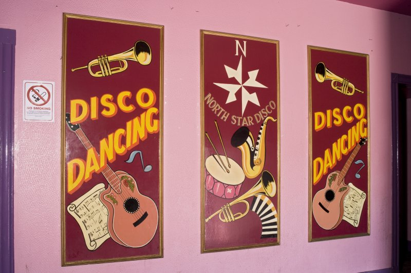 Interior view of North Star Cinema, Lerwick. Ground floor, foyer, detail of 'Disco' posters on wall