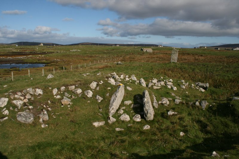 View of chamber and passage from SSW, with standing stone to NE of cairn.