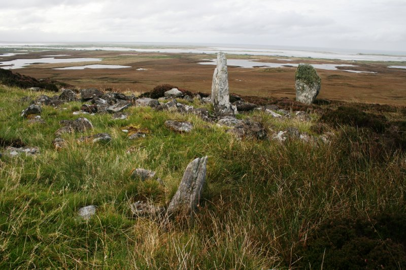 View of the standing stone and the SSW side of the cairn.