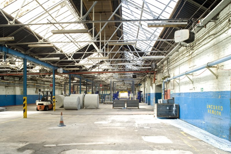 Interior. Foundry (building 2) from SE. Current machinery for cutting foam floor covering underlay. The area would have been divided into foundry area, power plant, plating and polishing when opened in 1913.