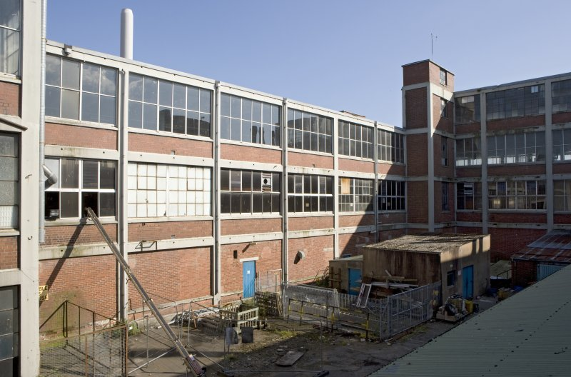 Main building, courtyard between blocks C and D, second phase, elevated view from N. The structure of the building (despite replaced windows) can be seen clearly: concrete frame with pre-cast holes for brackets etc., brick infill and maximum glazing. The lift shaft is visible on the right. This would have been big enough to take raw materials between floors. Larger lift shafts were built onto the the south facade and these would have carried cars from floor to floor during manufacture.