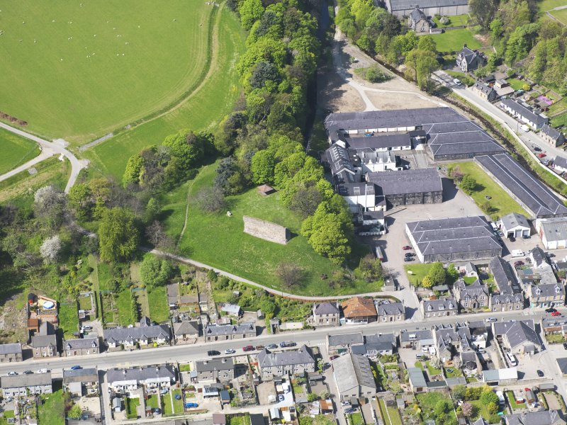 Oblique aerial view of Rothes Castle and Glen Spey Distillery, taken from the ESE.