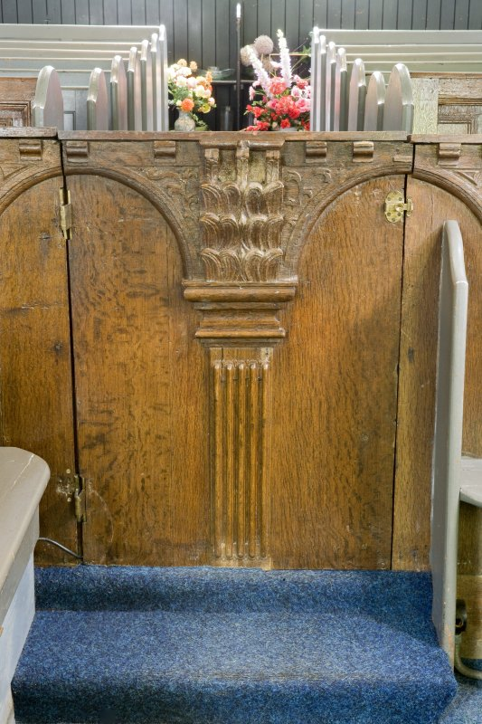 Interior. N range. Carved pew front. Detail