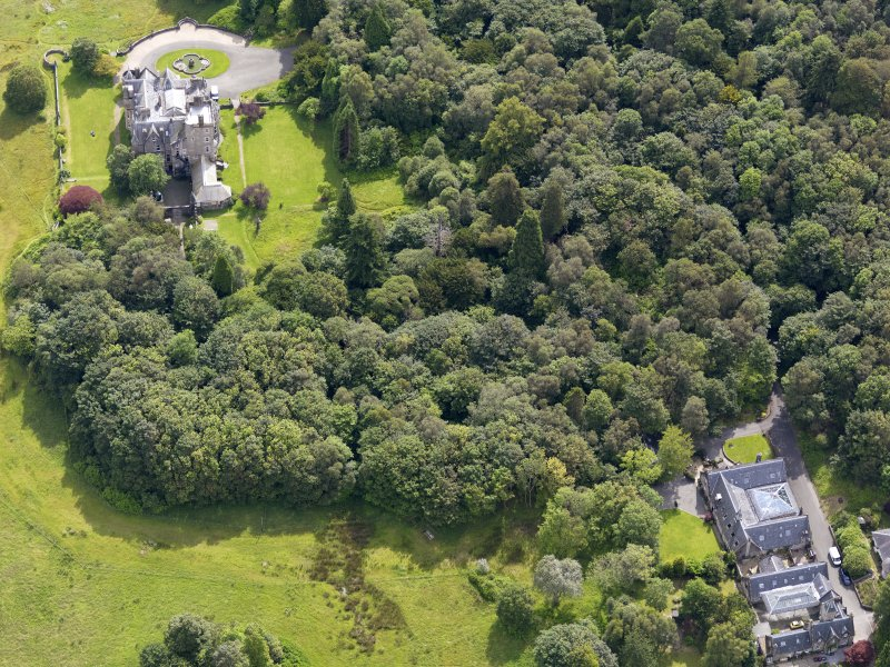 Oblique aerial view of Auchendennan Castle and stables, taken from the WNW.