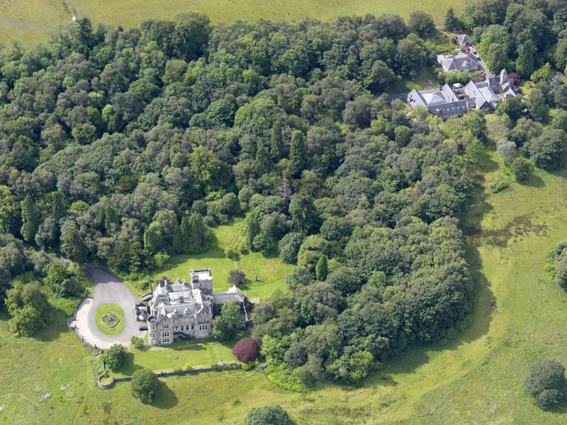 Oblique aerial view of Auchendennan Castle and stables, taken from the NE.