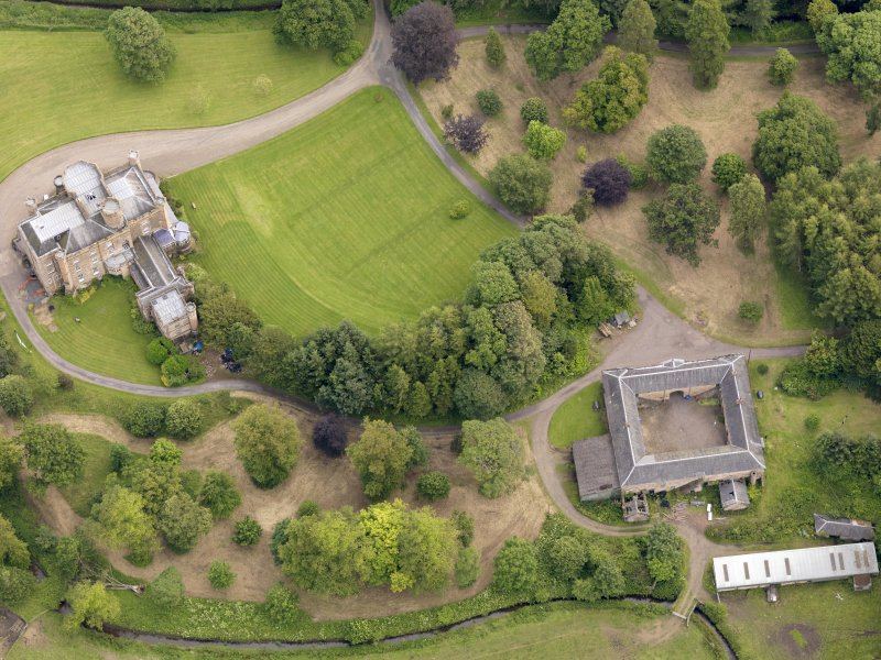 Oblique aerial view of Caprington Castle and stables, taken from the NW.