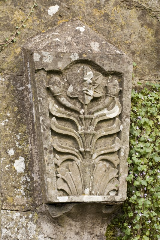 Detail of carved stone fragment set into wall adjacent to gate in garden to south of house.
