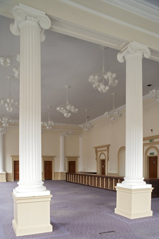 Interior. 1st floor, main hall, view through columns to SW