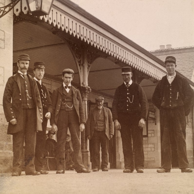 View of six men, some in railway uniform, on station platform, possibly in Stanley.