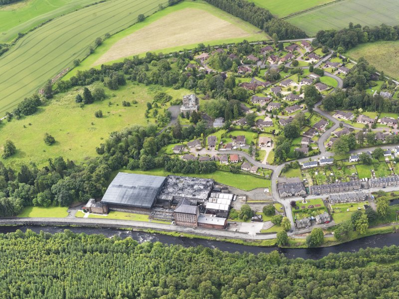 Oblique aerial view of Deanston Mills, taken from the NE.