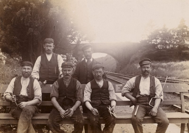 View of five railwaymen with bridge in background, possibly near Stanley.