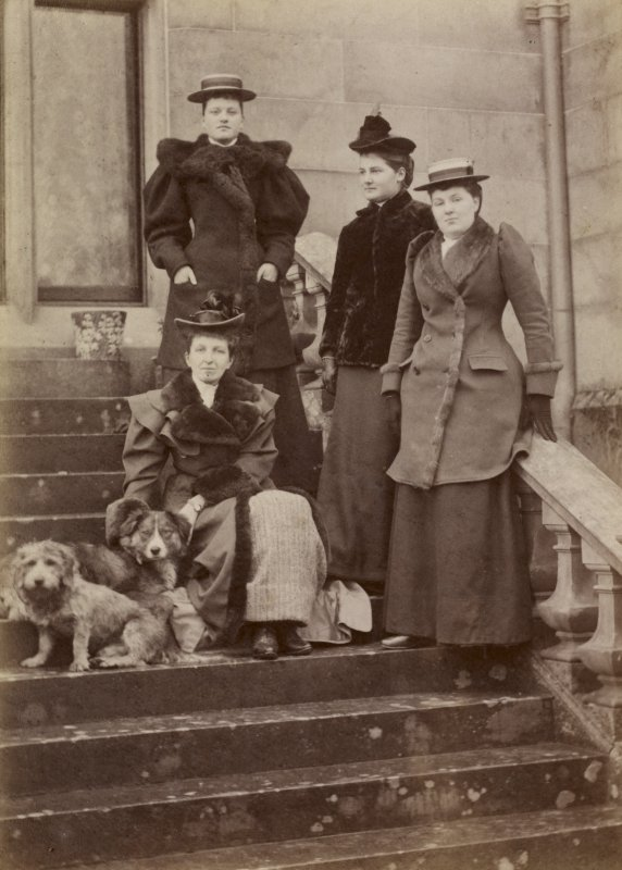 View of group of four ladies with two dogs probably at St Fort House.