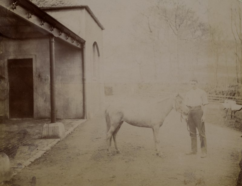 View of man with pony outside stables at St Fort House.