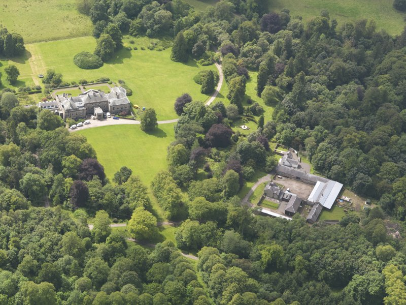 Oblique aerial view of Springkell House and stables, taken from the NE.