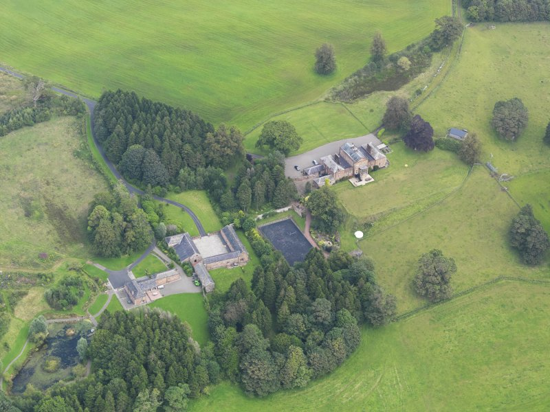 Oblique aerial view of Mossknowe House and policies, taken from the SW.