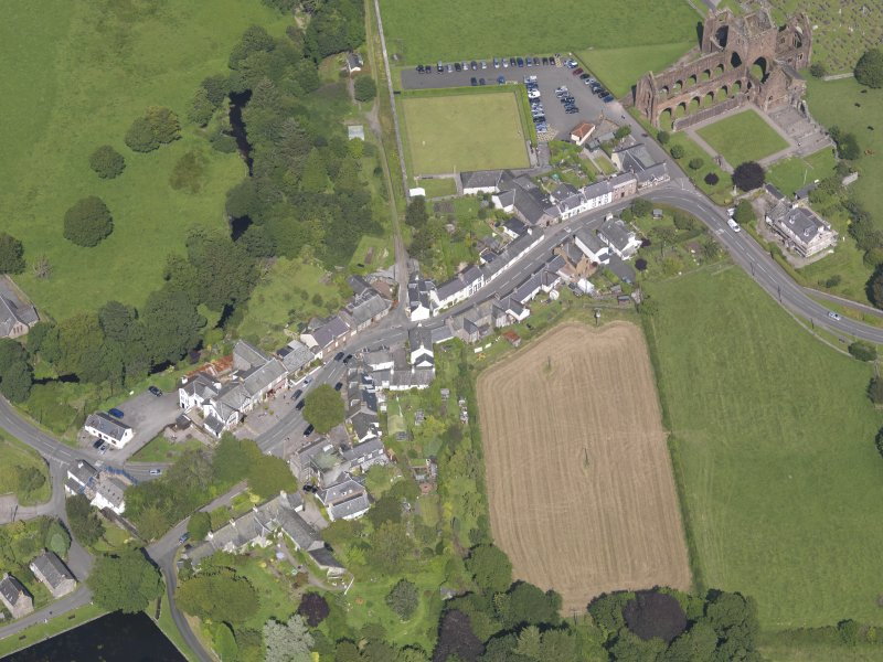 Oblique aerial view of New Abbey, centred on Main Street, taken from the SW.