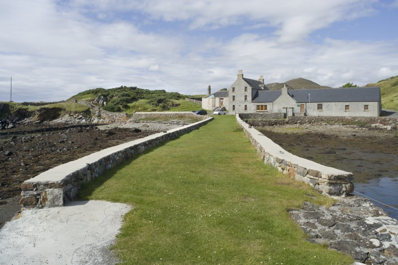 View of Rodel Hotel, Harris, looking along south wall of harbour, from south-east.