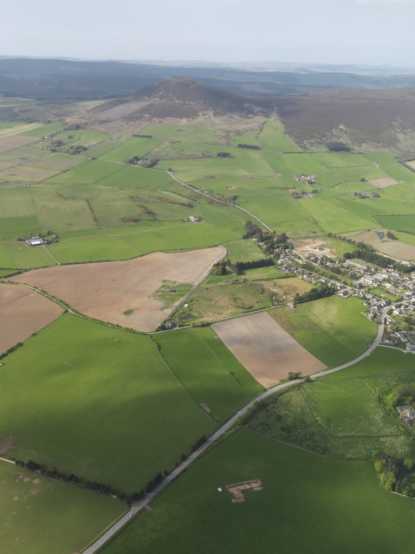 General oblique aerial view looking across the excavation of the enclosures at Barflat, with Rhynie village and Tap O'Noth beyond, taken from the SSE.