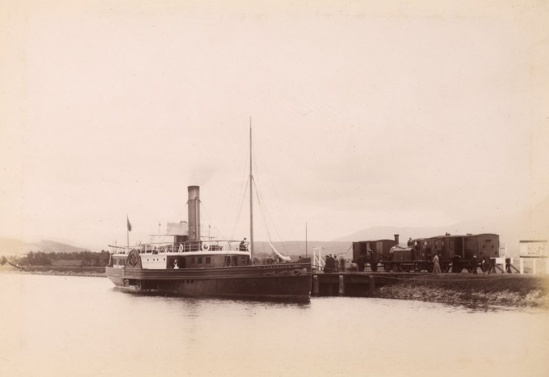 View of paddle steamer and train. Titled: 'Banavie.'