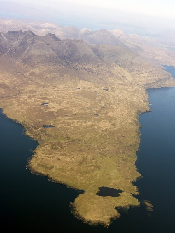General oblique aerial view of the remains of the harbour at Rubh' an Dunain, looking towards the Cuillins, Isle of Skye, taken from the W.