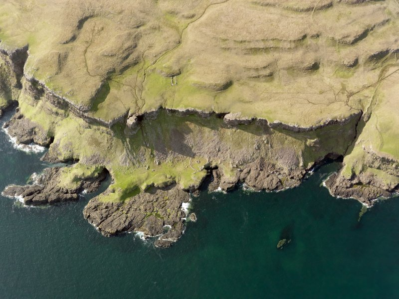 Oblique aerial view of the monastic settlement at Sgor nam Ban-Naomha, Canna, taken from the SSE.