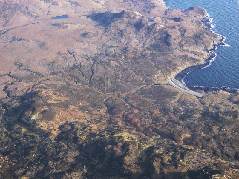 General oblique aerial view of the remains of the township at Usinish Bay, sheilings at Scalavat and nearby field boundaries and lazy beds, S Uist, taken from the W.