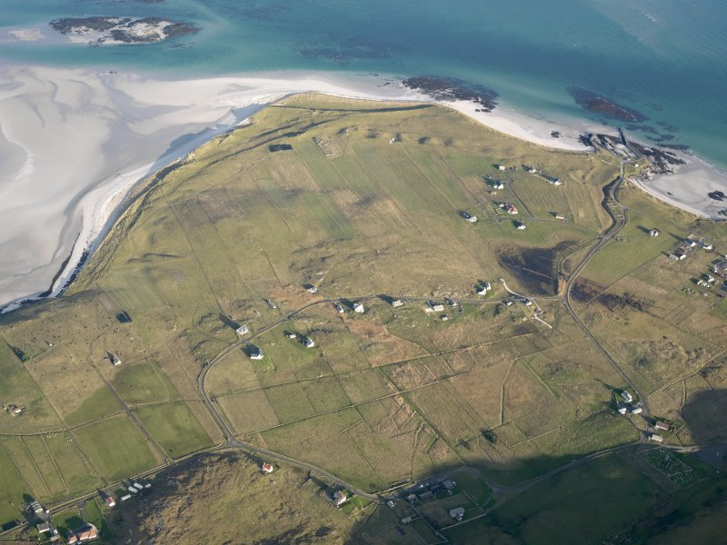 General oblique aerial view of the remains of the field system at Eoligarry, including the remains of a chapel and burial ground, looking towards the pier, Barra, taken from the SW.