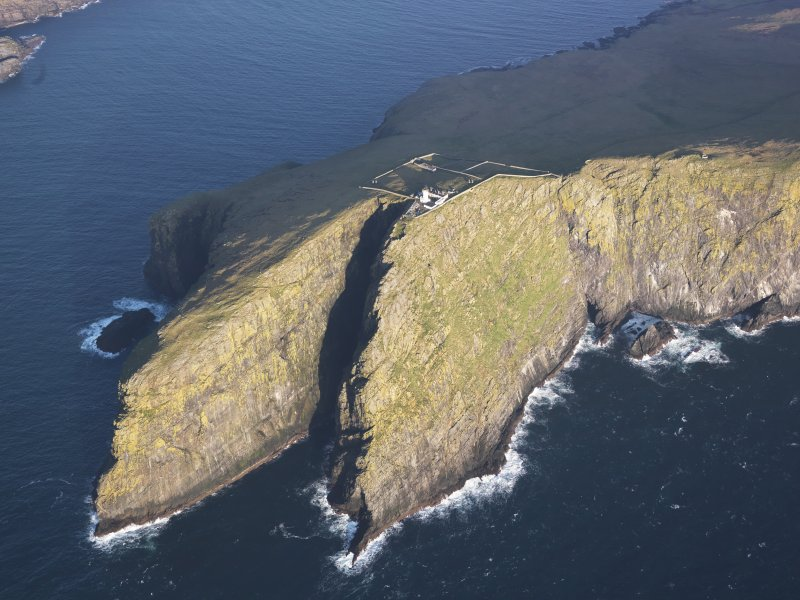 Oblique aerial view of  the remains of  Dun Briste and Sron an Duin, near Barra Head lighthouse overlooking the sea cliffs of Berneray, taken from the SW.
