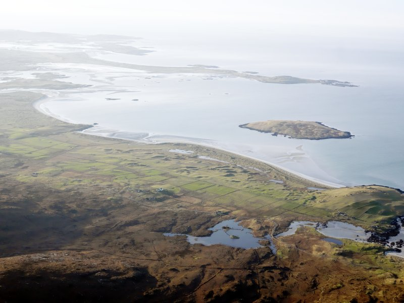 General oblique aerial view of the remains of Dun an Sticer, the remains of the township of Clachan Ard and the nearby head dyke, field system and lazy beds at Port nan long, North Uist, taken from the ESE.