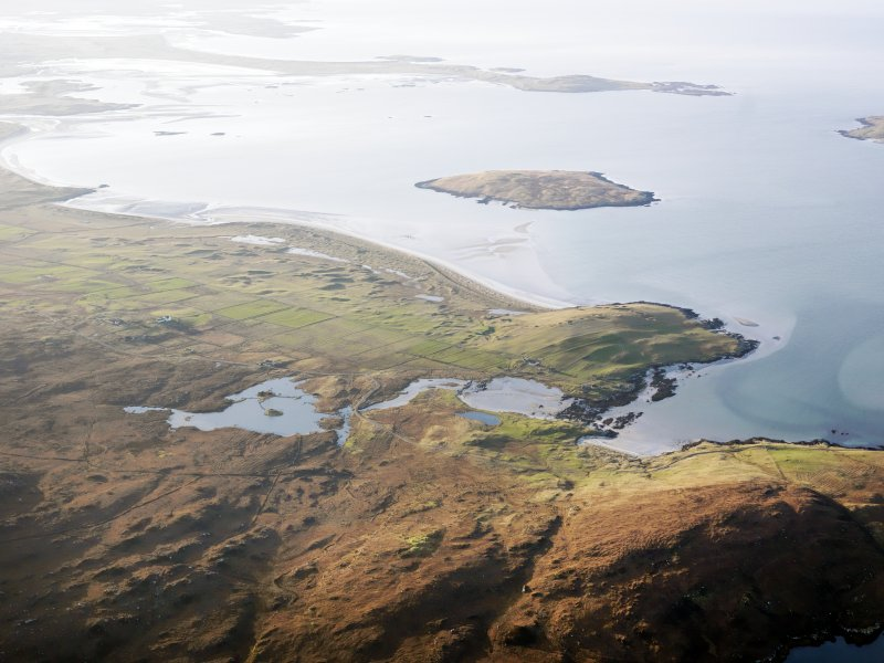 General oblique aerial view of the remains of Dun an Sticer, the remains of the township of Clachan Ard and the nearby head dyke, field system and lazy beds at Port nan long, North Uist, taken from the E.